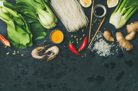 Flat lay of Asian cuisine ingredients over black background  copy space