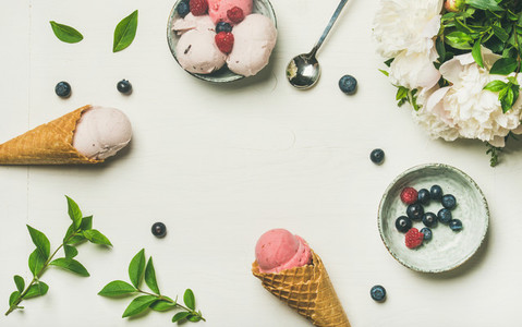 Ice cream scoops  peonies and berries over white background