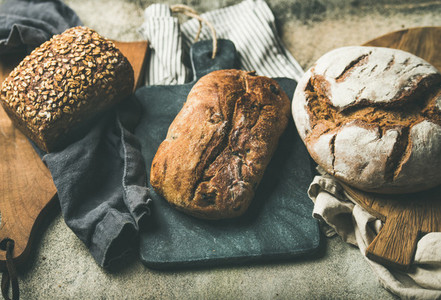 Various bread loaves on grey concrete background