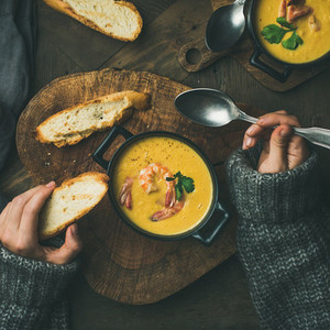 Woman in sweater eating corn soup with shrimps square crop