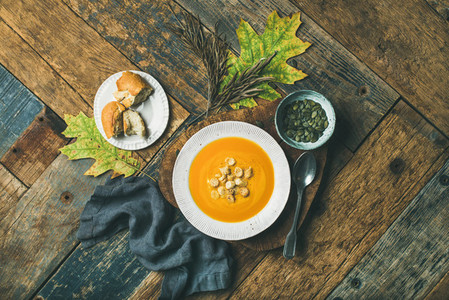 Warming pumpkin cream soup with croutons and seeds top view
