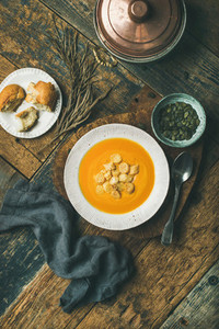 Warming pumpkin cream soup with croutons and seeds vertical composition
