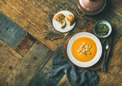 Warming pumpkin cream soup with croutons and seeds  copy space