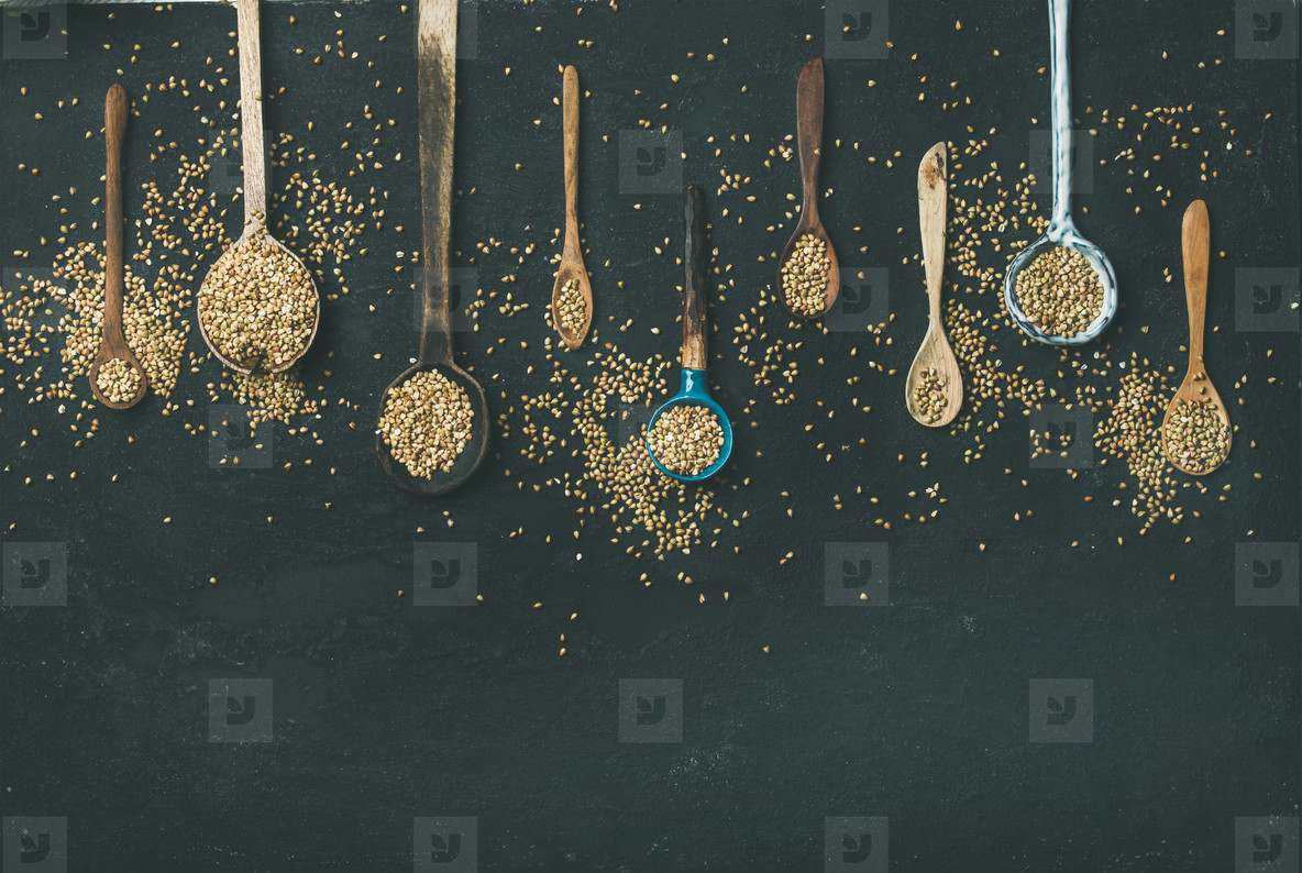 Various vintage kitchen spoons and green buckwheat grains