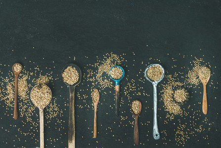 Various kitchen spoons full of green buckwheat grains copy space