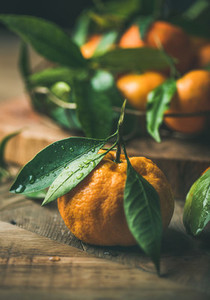 Fresh tangerine with leaves over wooden background close up