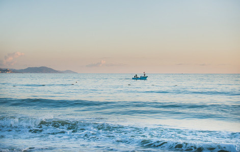 Calm Mediterranean Sea and boat at sunset pastel colors