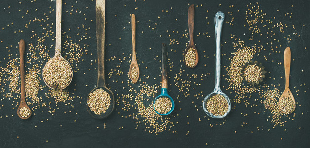 Various kitchen spoons full of green buckwheat grains  top view