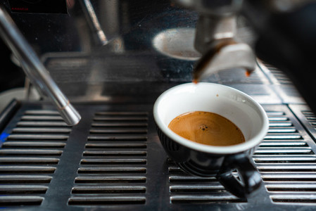 Little cup of espresso standing in the steel coffee machine