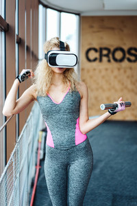 Beautiful girl in the gym with VR headset