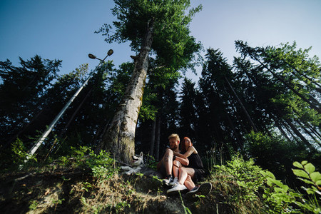 beautiful couple sitting in a forest near the tree