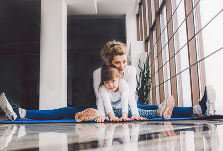 Mother and daughter hugs and stretch in the gym