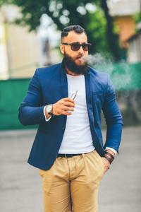 man with a beard smokes electronic cigarette