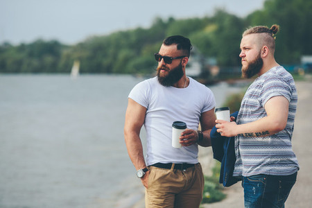 Two men stand and drink coffee