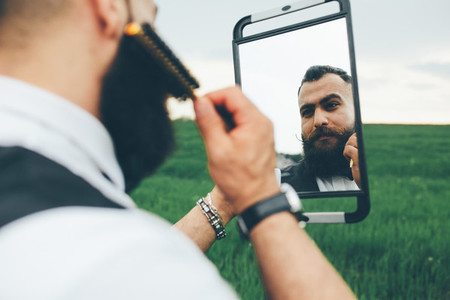 bearded man preparing to shave in the field