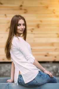 girl posing against background of a wooden wall