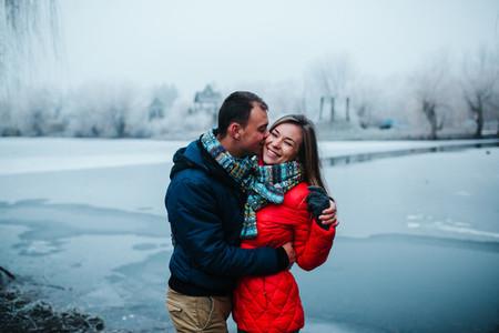 beautiful couple posing near a frozen river