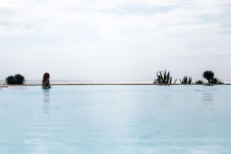 Young redhead woman in an infinity pool near the ocean