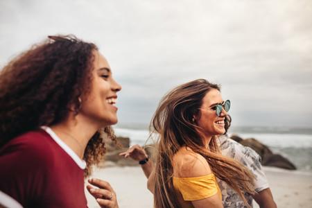 Beautiful woman with friends having fun on the beach