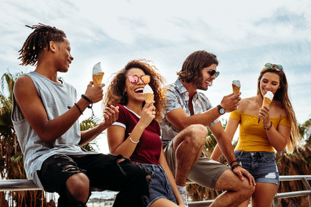Smiling young friends eating ice cream outdoors