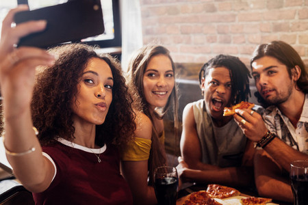 Diverse group of friends enjoying meal and taking selfie