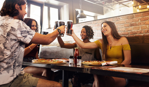 Multi ethnic group of friends toasting soft drinks at cafe