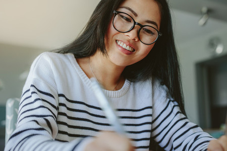 Smiling girl with eyeglasses studying at home