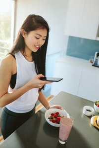Chinese woman capturing photos of a healthy breakfast