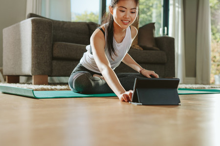 Woman using digital tablet while exercising at home