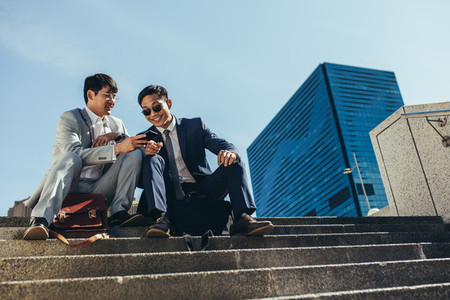 Businessmen sitting on the steps outside using smart phone