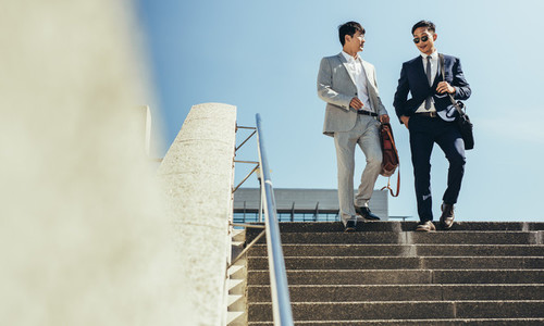 business men walking down the steps and talking