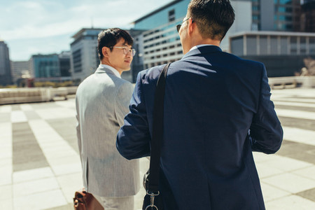 Two businessmen talking and walking in the city