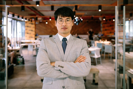Successful businessman standing at coffee shop door