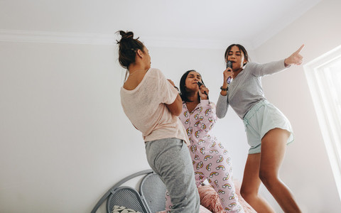Girls at a sleepover singing and dancing