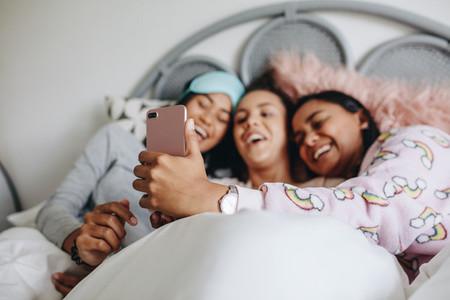 Three girl friends having fun during a sleepover
