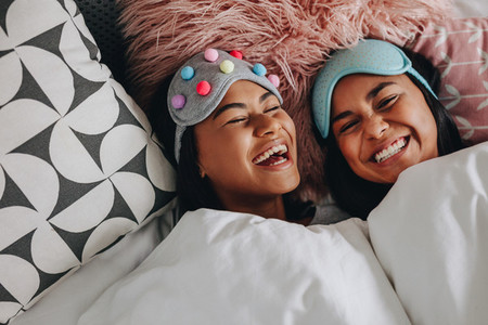 Happy girl friends laughing lying on bed