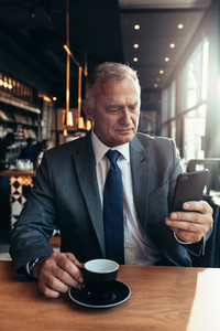 Senior entrepreneur at cafe texting on smartphone