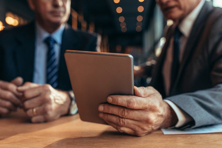 Digital tablet in hand of businessman talking to his partner