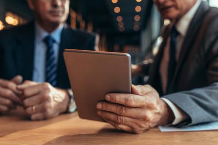 Digital tablet in hand of businessman talking to his partner