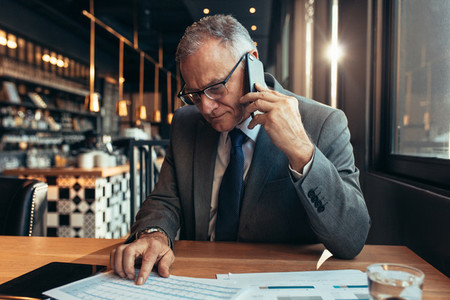 Senior businessmen discussing business figures over phone