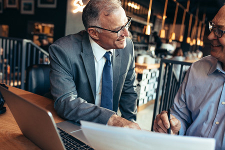 Senior businessmen meeting in a modern coffee shop