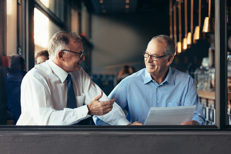 Mature business partners working together at a cafe