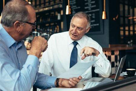 Men discussing business reports at cafe