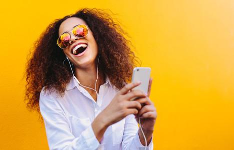 Laughing woman enjoying listening music