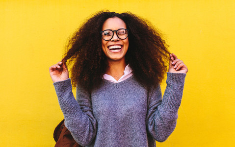 Laughing curly haired woman on yellow background