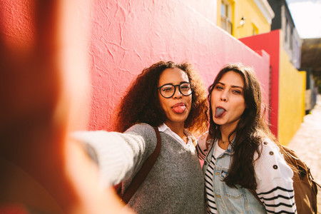 Girls with coloured tongue taking selfie