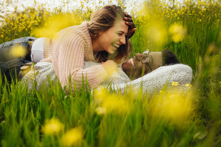 Interracial couple lying on grass and laughing