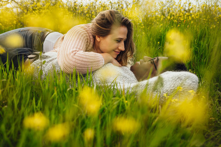 Young couple lying on the high grass