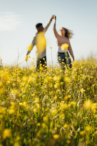 Romantic couple dancing in meadow of yellow flowers