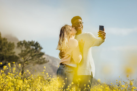 Romantic couple standing outdoors taking selfie